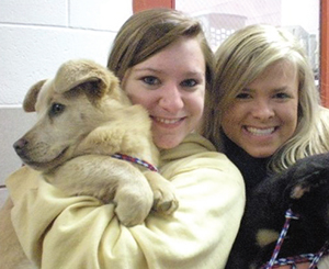 Two students holding a puppy